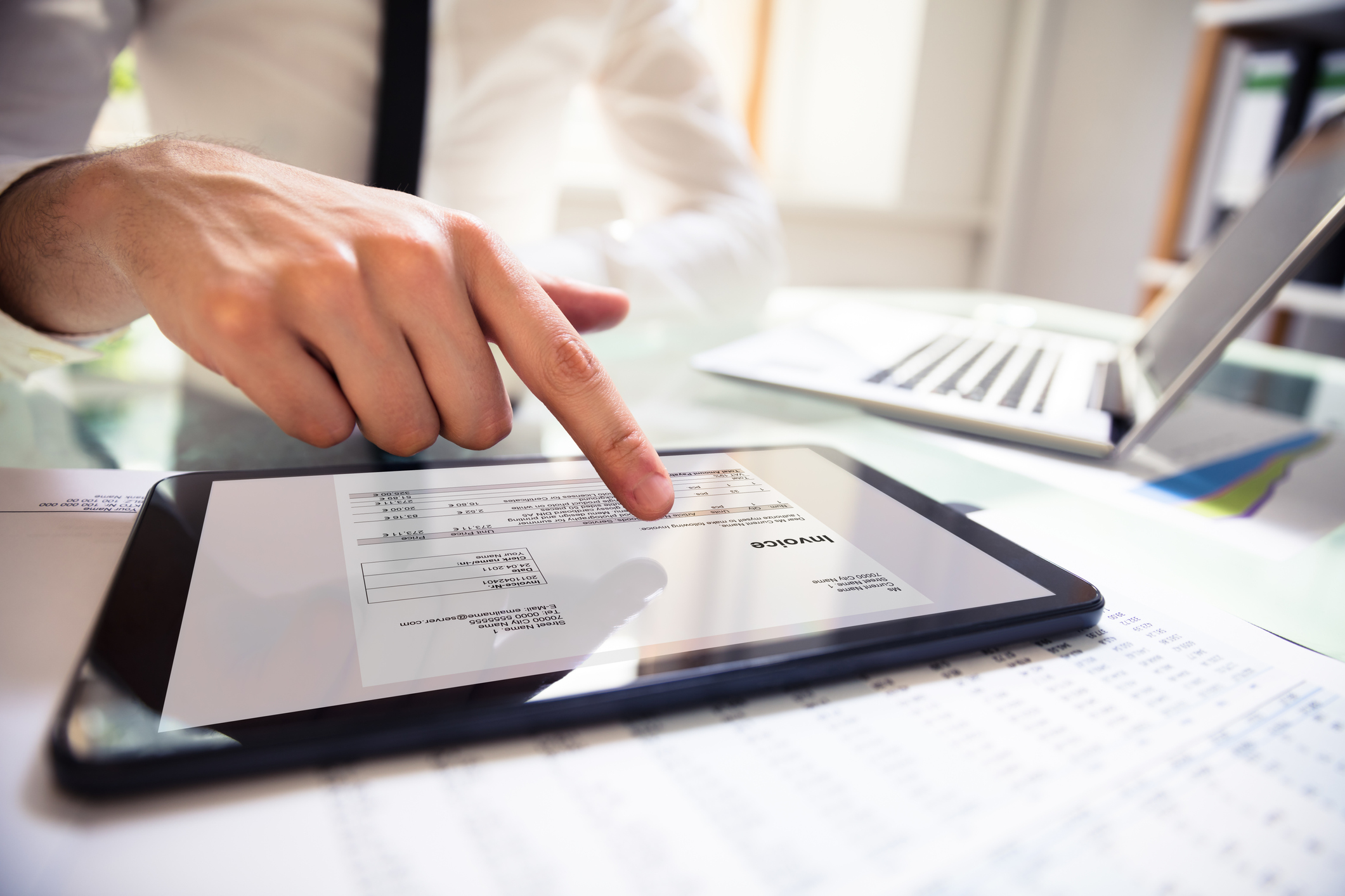 hand using tablet showing invoice document