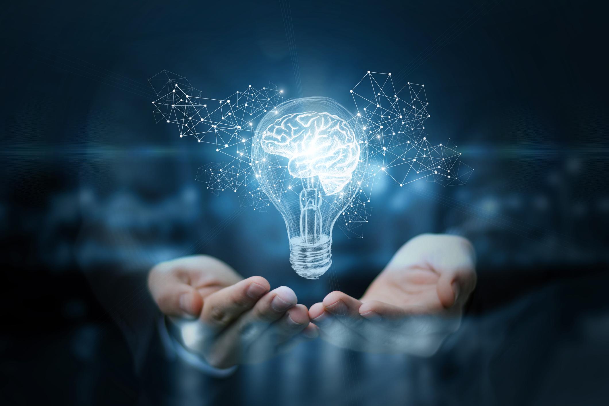 hands presenting illustration of light bulb with brain inside