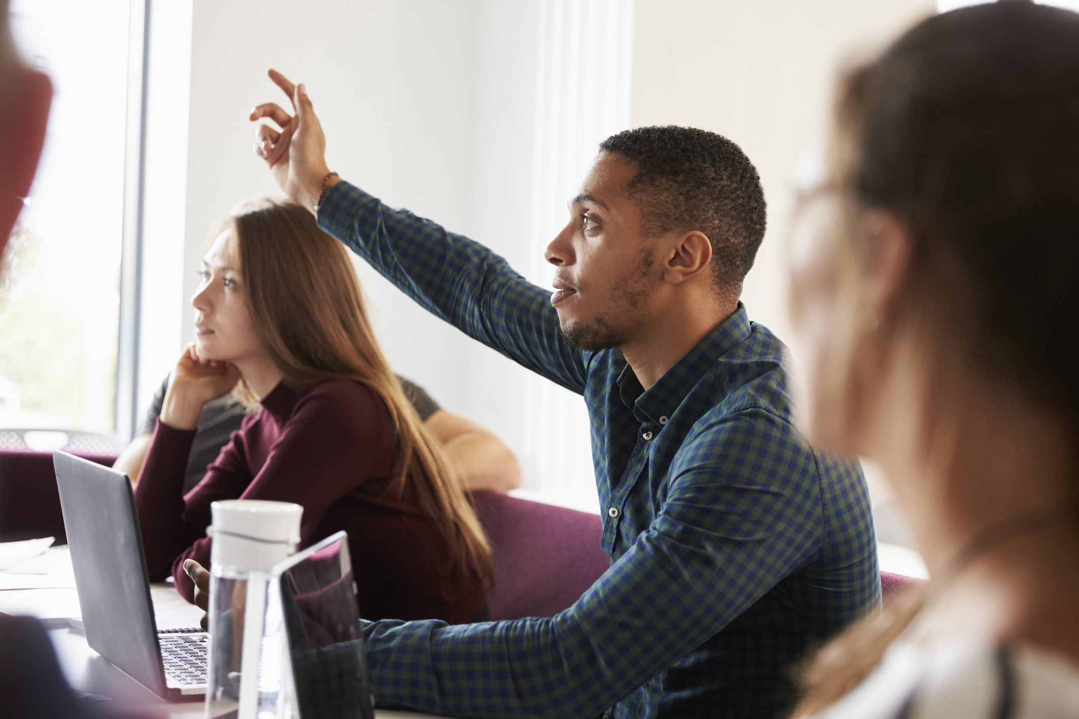 Student raising his hand in a university lecture hall