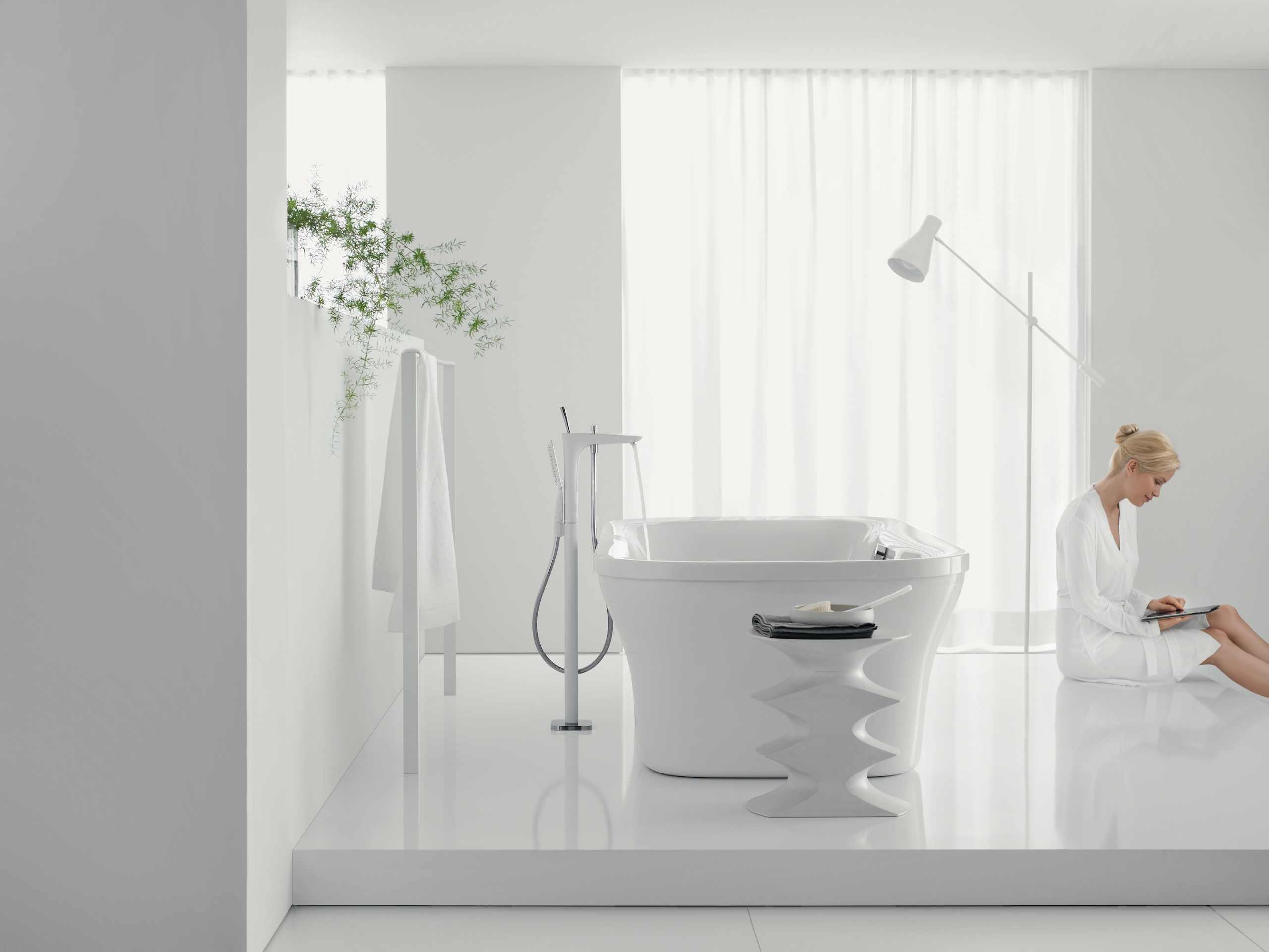 woman sitting in modern clean white bathroom with tub and lamp